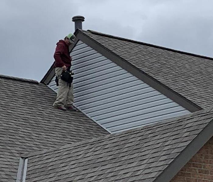 Worker standing on black roof next to the siding that has been replaced