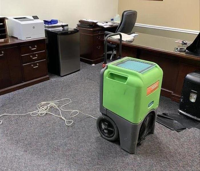 Office with gray carpet and green SERVPRO machine
