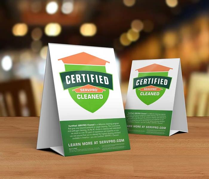 Table tent signs describing the Certified: SERVPRO Cleaned program on top of a wooden table